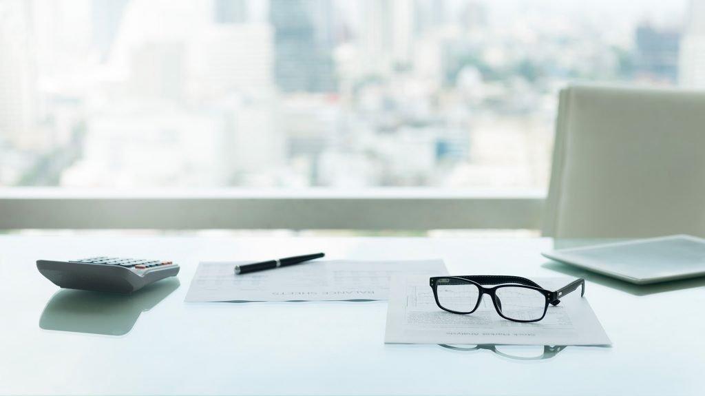 Occhiali con calcolatrice e taccuino sulla scrivania del manager aziendale con vista sulla città.